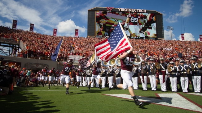 Sam Rogers (45) carries the American flag to lead the Hokies into Lane Stadium for the first time this year.